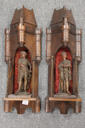 A pair of early twentieth century carved oak castelated wall brackets, each with standing spelter figures carrying swords, height 58 cm. (2)