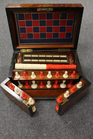 An early twentieth century burr yew wood games compendium, with compartmentalised interior, width 33 cm.