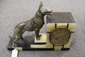 A French Art Deco onyx and marble clock, mounted with a metal dog, width 40 cm.