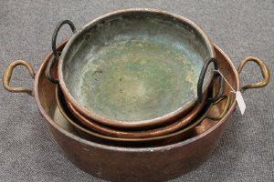Four French copper twin-handled pans. (4)
