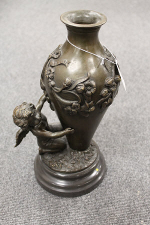 A bronze vase mounted with a cherub, on marble plinth, height 34.5 cm.