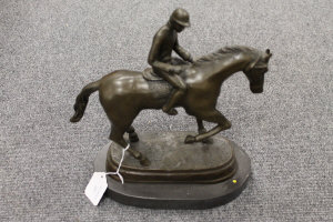 A bronze study of a horse and jockey with foot raised, on marble plinth, height 33 cm.