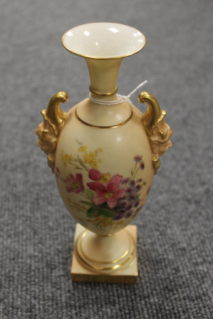 A Royal Worcester blush ivory gilded urn decorated with flowers, height 20.5 cm.