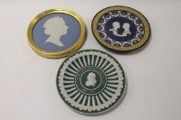 A Wedgwood plaque depicting the profile of Queen Elizabeth II, in blue and white jasper ware, width 19 cm, framed, together with two trophy plates, all boxed. (3)