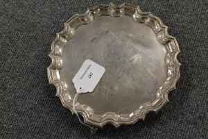A silver card tray with scalloped edge, width 21 cm.