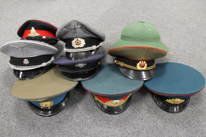 A collection of eight military caps - Russian, British, American, German and one Pith Helmet.