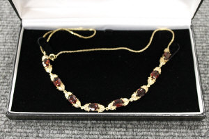 A 9ct gold necklace set with eight garnets.