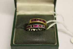 An 18ct gold five stone ruby ring, together with a white gold ruby eternity ring. (2)