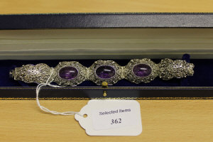 A sterling silver ornate filigree bracelet set with three cabochon amethysts.