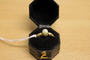 A pearl and diamond ring mounted in yellow metal.