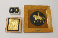 A Wedgwood medallion depicting Queen Elizabeth II on horse back, gilded black basalt, width 14 cm, framed, together with an Egyptian plaque and a pair of Royal Wedding boxes, all parts boxed. (3)