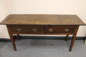 An early nineteenth century two drawer side table, on square tapered legs, width 154 cm.