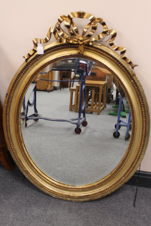 A nineteenth century gilded mirror, with bow decoration, height 103 cm.