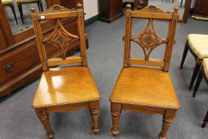 A pair of Victorian oak hall chairs. (2)