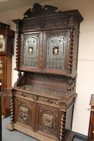 A late Victorian carved oak hunting cabinet, width 134 cm.