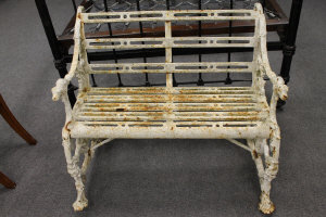 A Victorian cast iron garden seat, decorated with dog head terminal arms, width 94 cm.