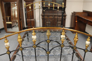 A late Victorian 4'6 cast iron, lacquered brass and ceramic bed stead.