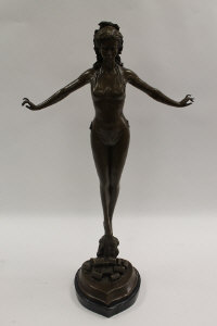 After Jules Juan - A slender lady standing on rocks, bronze study on black marble base, height 72 cm.