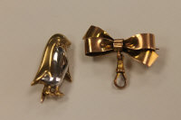 A 9ct two-tone gold penguin brooch, together with a ribbon bar brooch, 8.1g. (2)