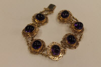 A 9ct gold bracelet set with seven cabochon amethysts.