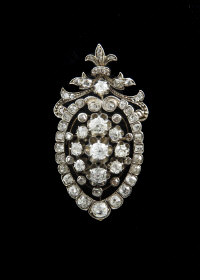 An impressive Victorian diamond cluster brooch, consisting of old cut diamonds mounted in shield form below a floral swag.