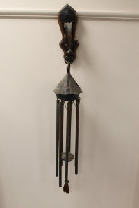 An Arts and Crafts copper wind chime, mounted on an oak bracket.