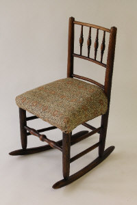 An early nineteenth century oak rocking chair, height 50 cm.