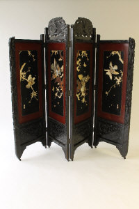 A late nineteenth century shibayama carved wooded four-fold screen, signed, height 183 cm.