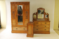 A late Victorian satin walnut mirror door wardrobe, together with the matching dressing table and bedside cabinet. (3)